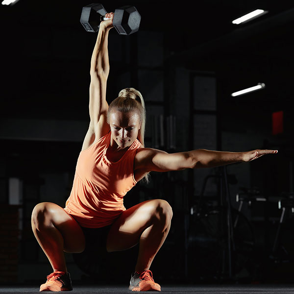 Woman doing CrossFit with a dumbell